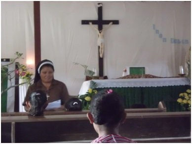 Sister Remy teaching catechism to the children in the parish church in Zumalai.